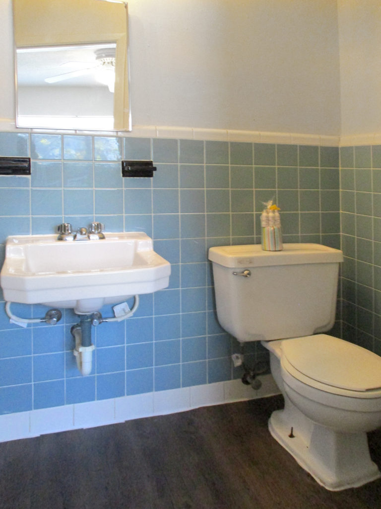 Blue tile bathroom with white sink and toilet - mirrored cabinet over sink