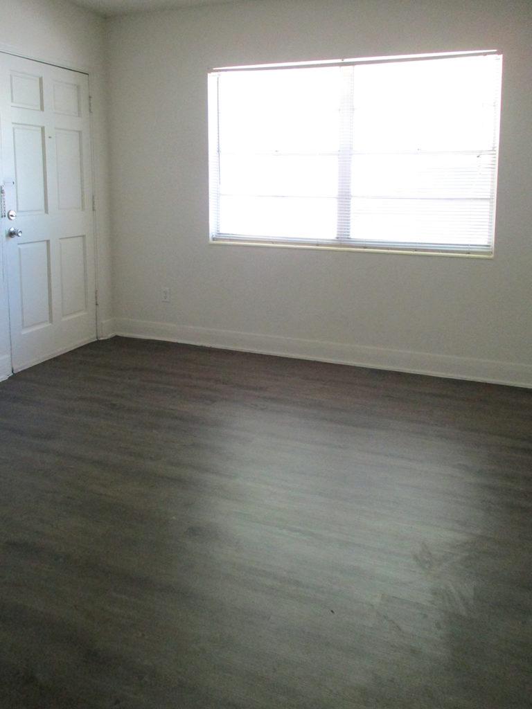 Living room with window, front door, and laminate flooring